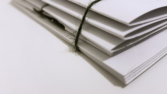 A stack of white paper folders.