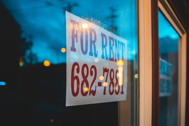 "A sign in the window saying ""For Rent""."