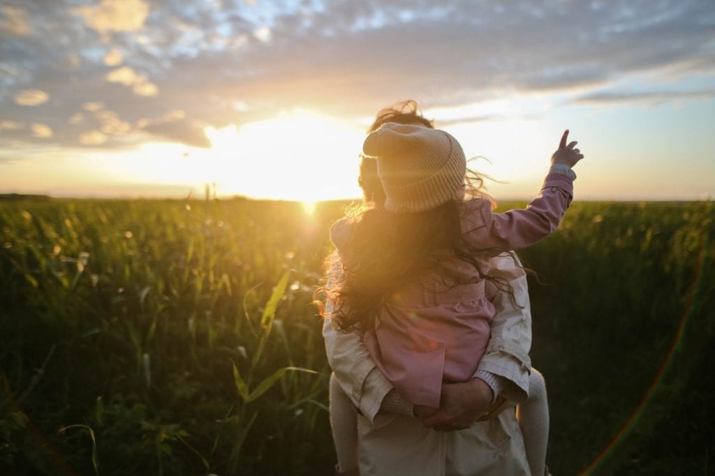A mother holding her daughter in the field at sunset, symbolizing one of the reasons why the demand for rural properties soars in the New York state