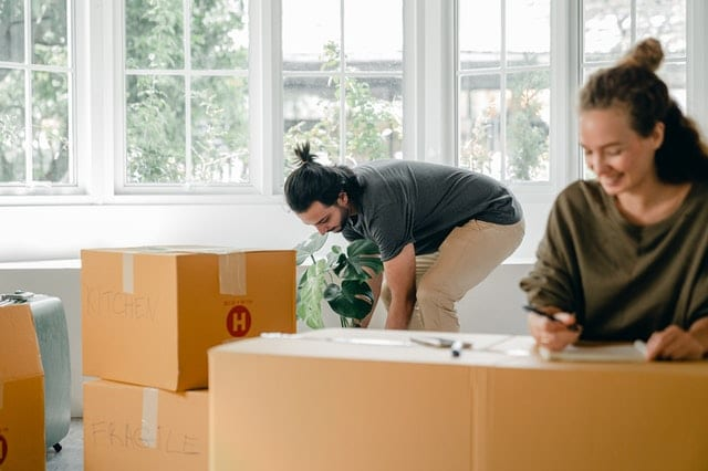 A woman and a man packing boxes for a relocation.