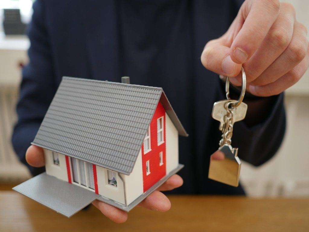A hand holding a model house and a key