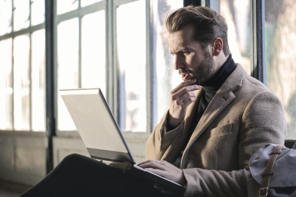 A man sitting in front of his laptop, thinking about whether to buy or rent office space in Detroit